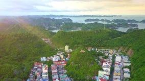 Solnedgången strålar den ljusa staden som placeras på ön med Hilly Jungle