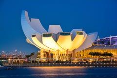 Solnedgången tänder över det Marina Bay Sands Amphitheatre och ArtScience museet i Singapore Royaltyfri Fotografi