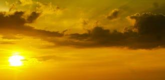 Solnedgången vid havet är ett guld- ljus Arkivfoton