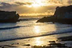 Solnedgången vid havet med vaggar och havsväxt Arkivbilder