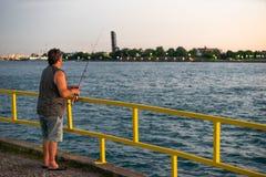 Solnedgångfiske av en pir arkivfoton