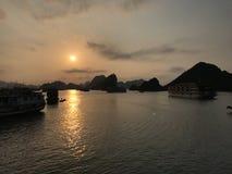 Solnedgångfjärd på den Halong fjärden royaltyfria bilder