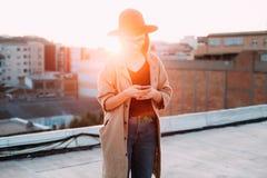 Solnedgångfoto av kvinnan som använder smartphonen arkivbilder
