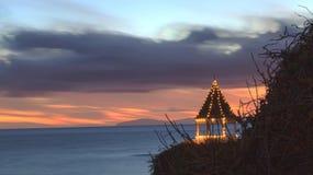Solnedgånggazebo på en klippa som förbiser havet Royaltyfria Foton