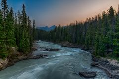 Solnedgångglöd över den grova floden och skog Royaltyfri Foto