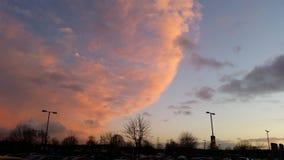 Solnedgångglöd i orange moln för vinterUK arkivbilder
