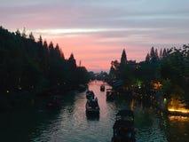 Solnedgångglöd med det lilla fartyget för tradional på floden i Wuzhen royaltyfri fotografi