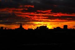 Solnedgångglöd och Silhouetted horisont av staden Royaltyfri Foto