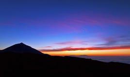 Solnedgångglöd ovanför molnen som silhouetting den Teide vulkan Arkivbilder