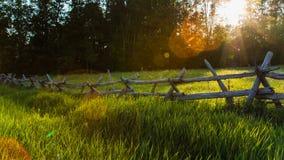 Solnedgånggräsfält med kluvna stångstaket Arkivfoto