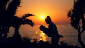 Solnedgånghav och en kvinna som lite spelar med pojken Fostra och behandla som ett barn, moderskapbegreppet arkivfilmer