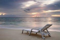 Solnedgånghav och strand med sunbed royaltyfri bild