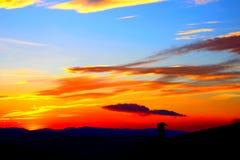 Solnedgånghimmel av det röda, gula och blåa färgspektret med moln royaltyfri fotografi