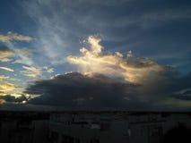 Solnedgånghimmel med moln över staden fotografering för bildbyråer