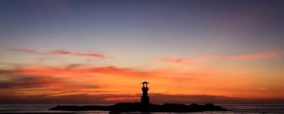 Solnedgånghimmel och en fyrkontur Arkivbilder