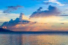 Solnedgånghimmel och hav Sjösidasolnedgång med apelsin- och blåttmoln Tropiskt hav och avlägsen ökontur arkivbilder