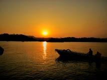 Solnedgånghimmel och sjö Arkivfoto