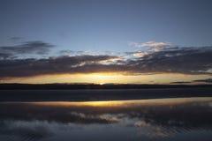 Solnedgånghimmel på sjön med moln arkivfoto