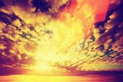 Solnedgånghimmel, sol som skiner till och med moln Tappning Arkivbild