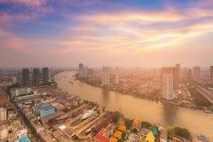 Solnedgånghimmelbakgrund över floden buktade och flyg- sikt för stad Royaltyfri Bild