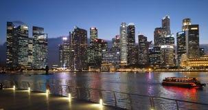 Solnedgånghorisont av Singapore cityscape som avspeglas i vatten arkivfilmer