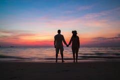 Solnedgångkonturn av barn kopplar ihop förälskat krama på stranden royaltyfri foto