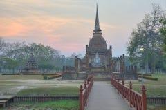 Solnedgånglandskap av Wat Sa Si i historiska Sukhothai parkerar med inställningssolen i bakgrund, en träbro i förgrund arkivbild