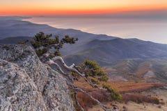 Solnedgånglandskap på ett högt berg som förbiser havet Arkivfoto