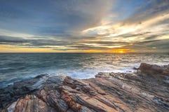 Solnedgångljus - orange inverkanvatten på stranden Arkivfoto
