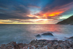 Solnedgångljus - orange inverkanvatten på stranden royaltyfri bild