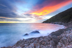 Solnedgångljus - orange inverkanvatten på stranden arkivfoton