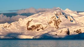 Solnedgångljus på snö-korkade berg och glaciärer, antarktisk halvö royaltyfri foto