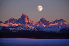 SolnedgångljusAlpen glöd på Tetons Teton berg med måneRisi fotografering för bildbyråer