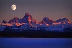 SolnedgångljusAlpen glöd på Tetons Teton berg med månestigning arkivbild
