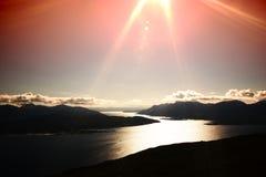 SolnedgångNorge fjordar med ljus läckakonturbakgrund Arkivfoto