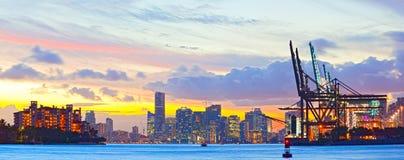 Solnedgångpanorama av Miami port, Fisher Island och i stadens centrum Royaltyfri Bild