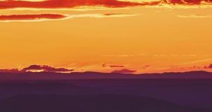 Solnedgångplats med solnedgången bak bergen och molnen i bakgrundstidschackningsperiod, varm färgrik himmel med mjuka moln lager videofilmer