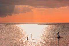 Solnedgångplats på kommande åskväderbakgrund Familjkonturer på solnedgången på havet En fader med tre barn paddlar på arkivbilder