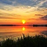 Solnedgångreflexion i den lugna sjön Fotografering för Bildbyråer