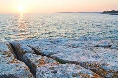 SolnedgångSeascape med vaggar arkivbilder