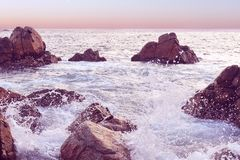 Solnedgångseascape på Sri Lanka Att krascha för våg vaggar Naturlig bakgrund i rosa signal arkivbilder