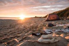 Solnedgångsemestersida med tältet och handdukar på stranden Royaltyfria Bilder