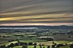 Solnedgångsikt över frodigt jordbruks- land royaltyfria foton