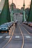 Solnedgångsikt av bilar och cyklisten på frihetbron på solnedgången i den Budapest Ungern Arkivbild