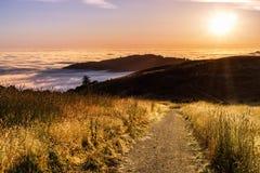 Solnedgångsikt av den fotvandra slingan i de Santa Cruz bergen; dal som täckas av ett hav av moln som är synliga i bakgrunden; Sa arkivbilder