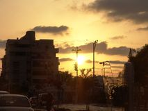 Solnedgångsikt av ett bås för stadgatatelefon, parkerade bilar och verkligt folk på deras väg fotografering för bildbyråer