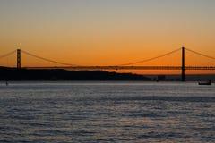 Solnedgångsikt av Tagus River Rio Tajo och 25th av April Bridge Arkivbilder