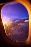 Solnedgångsikt från flygplanfönster Arkivfoto