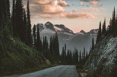 Solnedgångsikt från monteringen Revelstoke över skog med blå himmel och moln brittiska Kanada columbia fotografering för bildbyråer