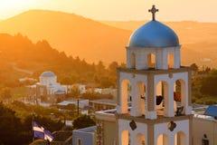 Solnedgångsikt med den kyrkliga klockstapeln Arkivfoton